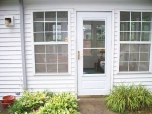 Storm door flanked by double hung windows - before
