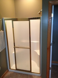 Before - small fiberglass shower with a skinny entry through a sliding glass door