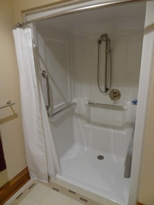 Kohler one piece roll in shower with hand held shower safety bars and fold down seat