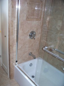 Durable ceramic tile with frameless tub door and Moen fixtures in Parma bath remodel