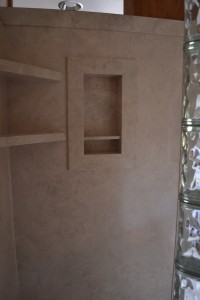 DIY creme travertine interior shower wall panels with corner shelf and recessed soap and shampoo niche
