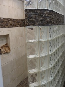 Close up of decorative tile border in a curved glass block shower wall
