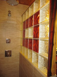 Inside view of shower with custom glass block wall and decorative paduk wood trim in a Texas remodel