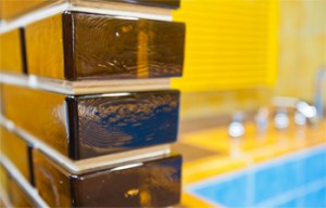 """Close up with """"siena"""" colored glass bricks installed with mortar  at a pool"""