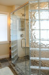 Frameless pivoting glass shower door with glass block walls