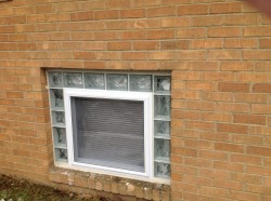 Vinyl hopper egress window surrounded by glass blocks