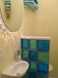 Small partition wall in a half bathroom using colored glass blocks