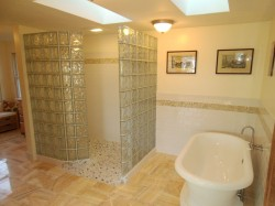 Glass block walk in shower with acrylic pedestal tub and white subway tile