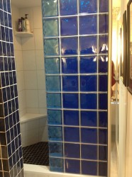 Striped colored glass block shower wall