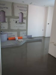 Concrete sloped base with no step over curb prior to glass block wall installation