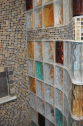 Inside curved and colored glass block shower with a tile row