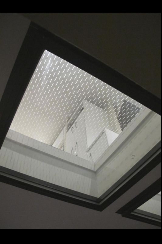 Glass floor panels from a patio looking up into a kitchen