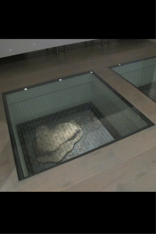 Looking down from a glass floor panel to a patio