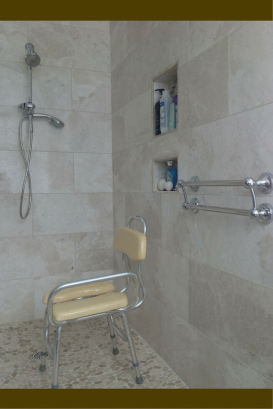 Hand held shower and decorative grab bar and lower niches in a handicap shower