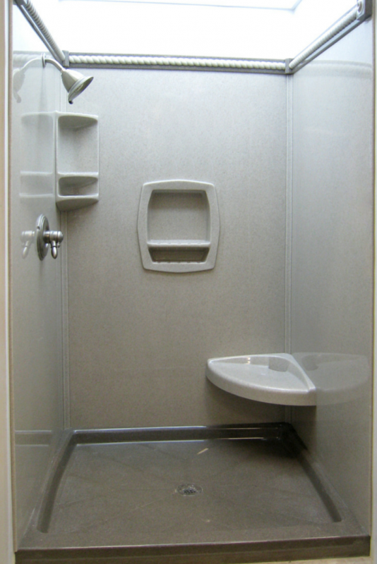 Solid surface shower wall panels with a corner seat and recessed niches