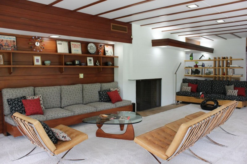 Built in living room redwood shelving adds to style and function in this Usonian home