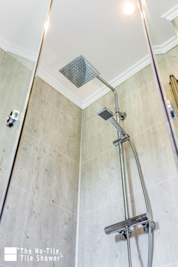 Rain shower head with cracked cement pattern laminated wall panels | Innovate Building Solutions