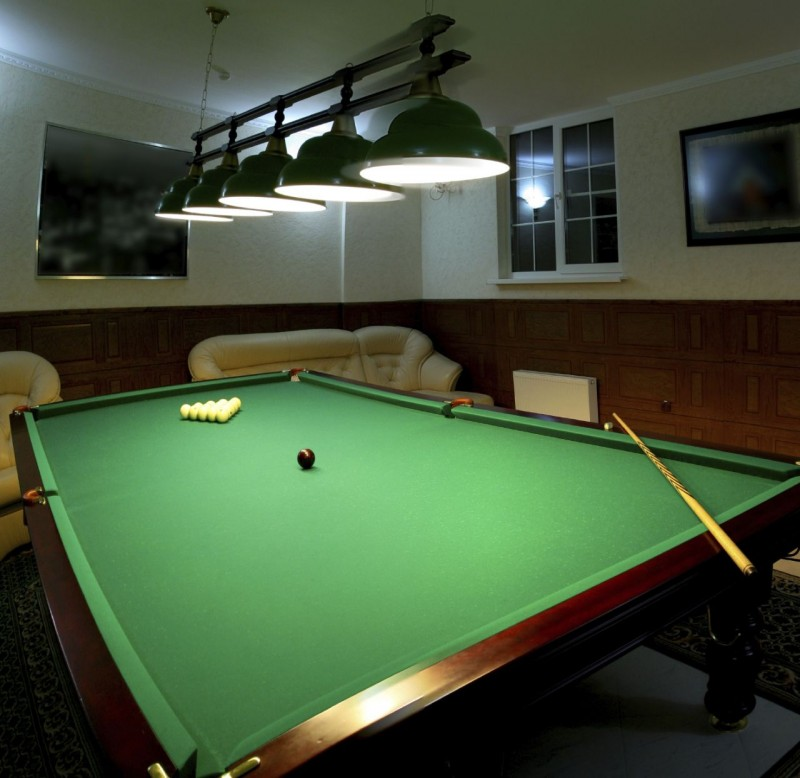 Pool table in a man cave with track lighting