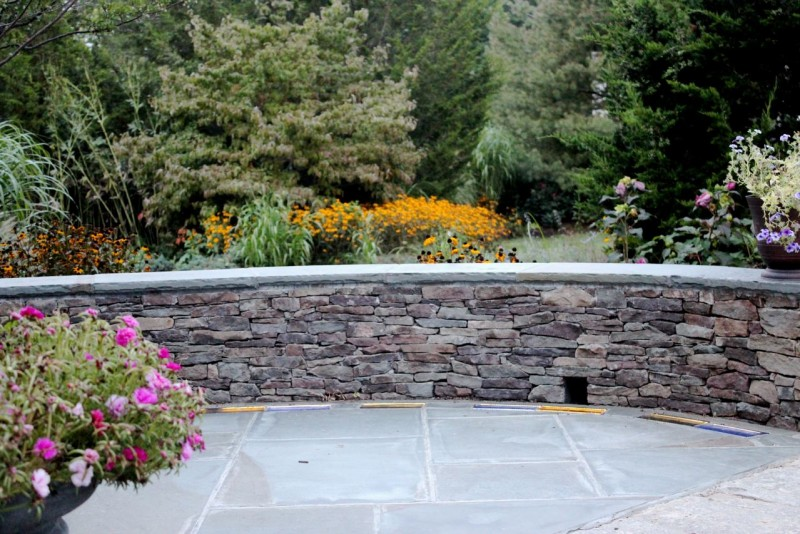 Curved stone retaining wall and colored glass pavers in a patio hardscape design in Guilford Connecticut