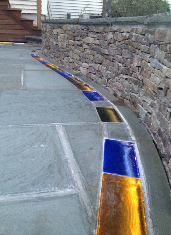 Solid colored glass brick pavers with LED lighting in a bluestone patio in Connecticut