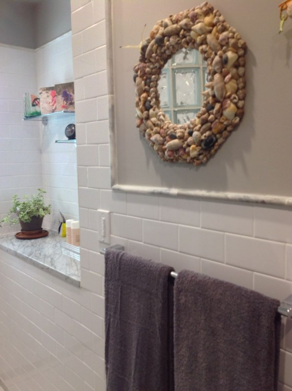 Decorative sea shell mirror with glass block wall reflection