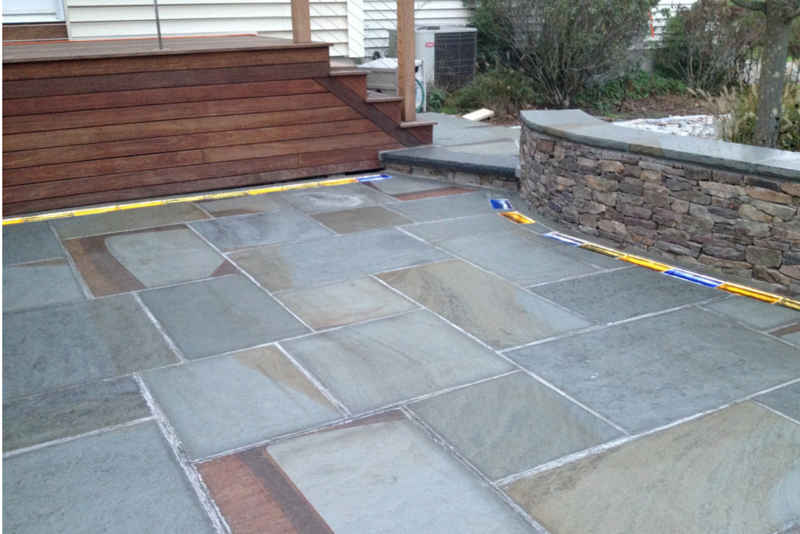 Pennsylvania bluestone laid in square and rectangular shapes with colored glass bricks in a custom home landscape design in Connecticut