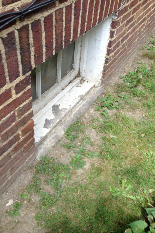 Deteriorated wood framed basement window frame