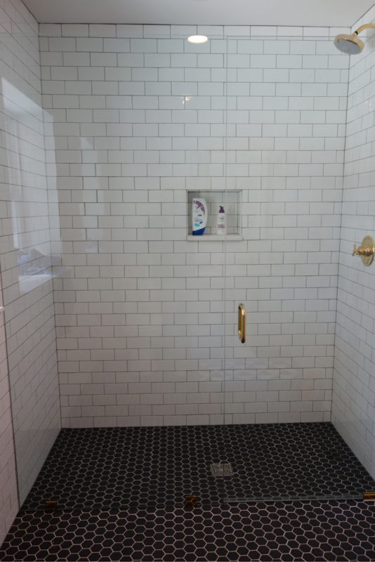 Roll in curbless shower with a frameless glass shower door. Using a shower screen which pivots inside and outside also makes a roll in shower warmer. | Innovate Building Solutions
