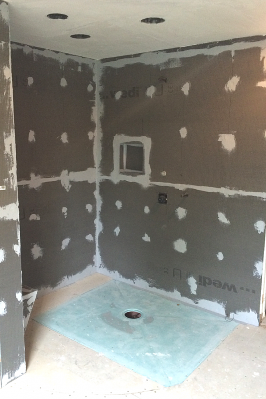 This barrier free wet room shower shows the waterproof tile wall board and shower base former during the installation process. The floor was not yet waterproofed. | Innovate Building Solutions