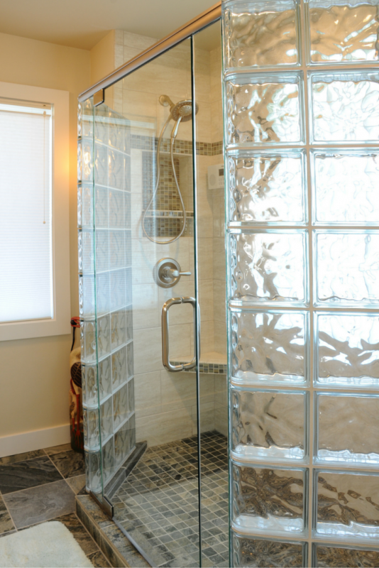 A glass block shower with a frameless glass door