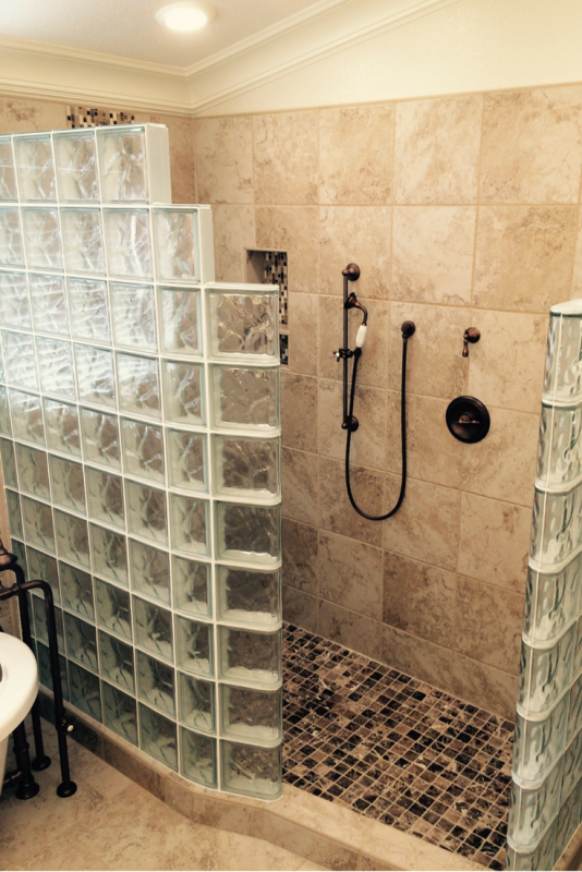 An open glass block shower which is only anchored on one side