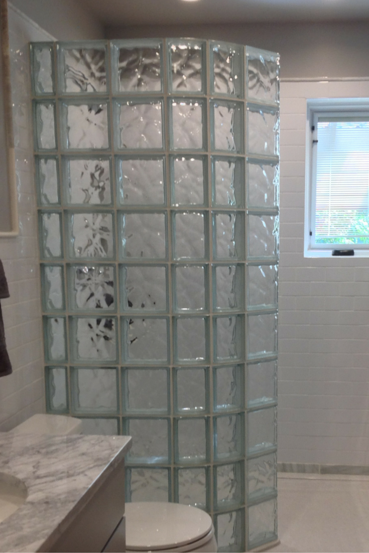 curved glass block wall keeps the water in for a walk in shower