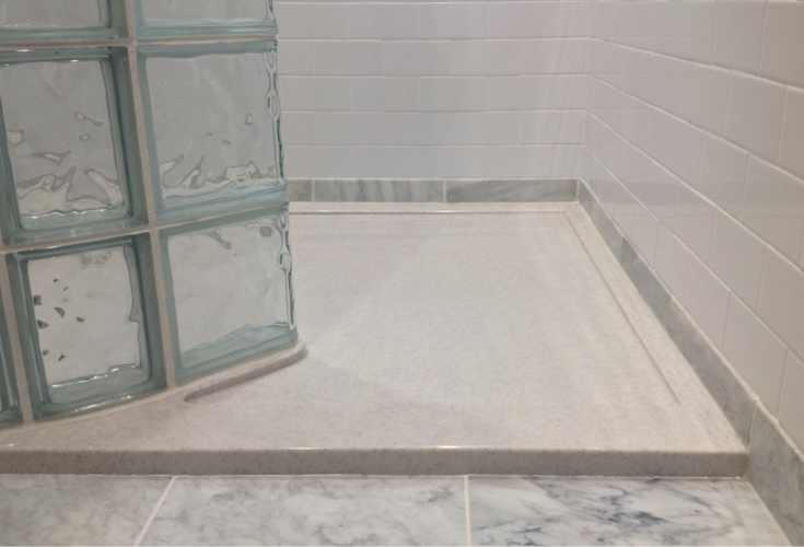 Low profile stone solid surface shower pan made for a glass block shower wall