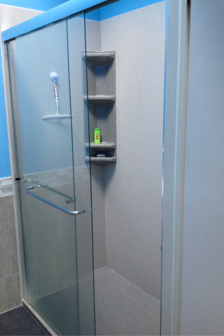 Tub to shower conversion with a stone solid surface shower wall panel and pan system