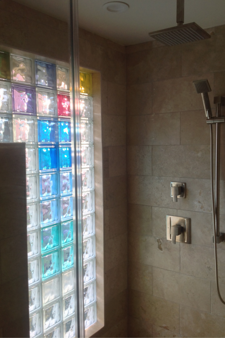 Colored glass block shower wall gives privacy and light for a small bathroom in columbus ohio