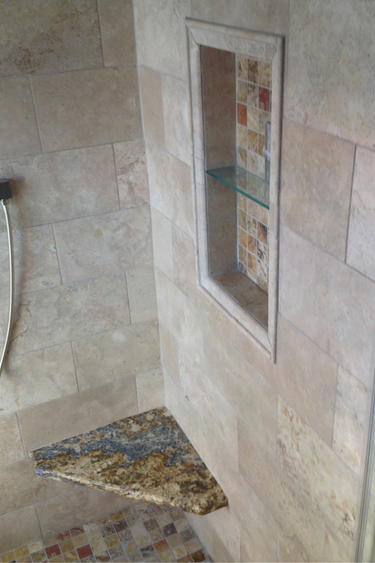 A Santa Cecilia Granite Shower bench seat adds light and color to a small columbus bathroom