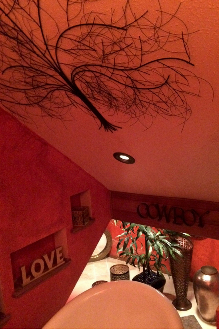 Artistic metal tree mural in a red colored bathroom in Santa Barbara California