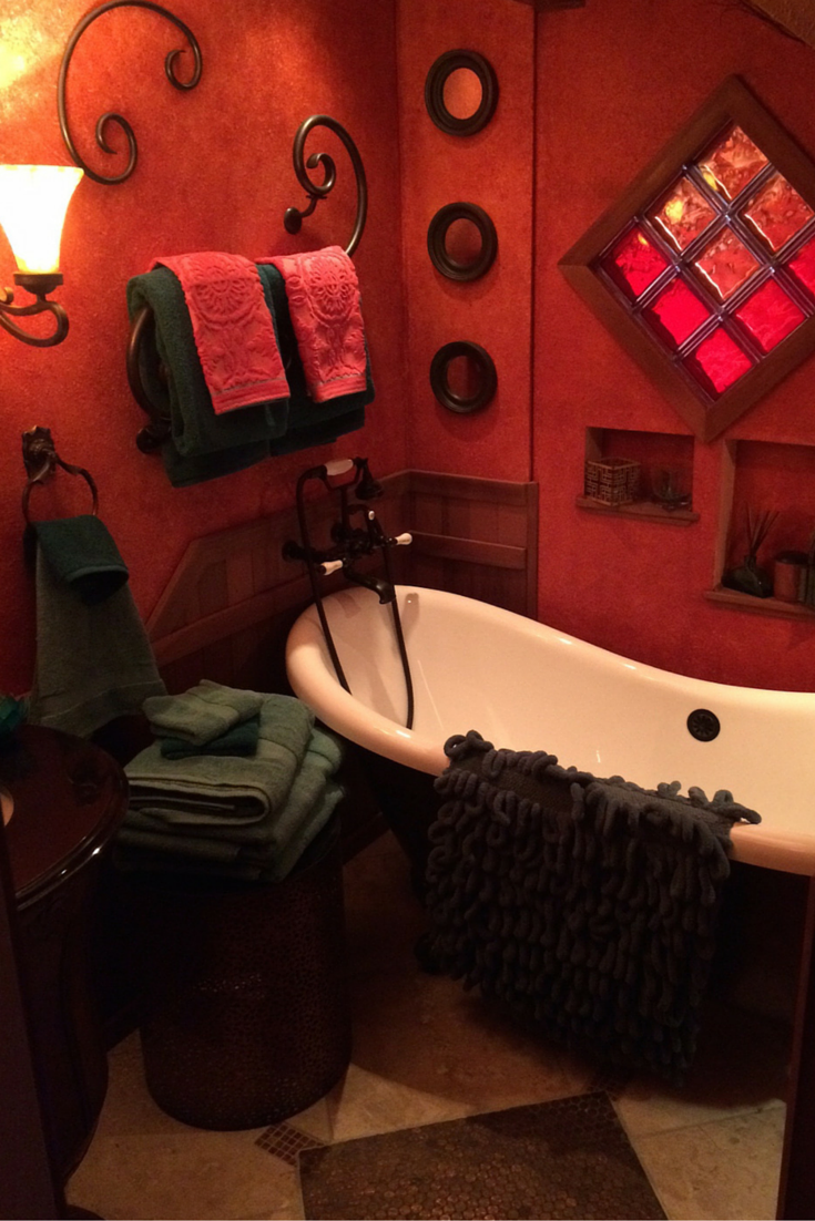 Custom remodeled bathroom with a clawfoot tub and red colored glass block window in Santa Barbara California