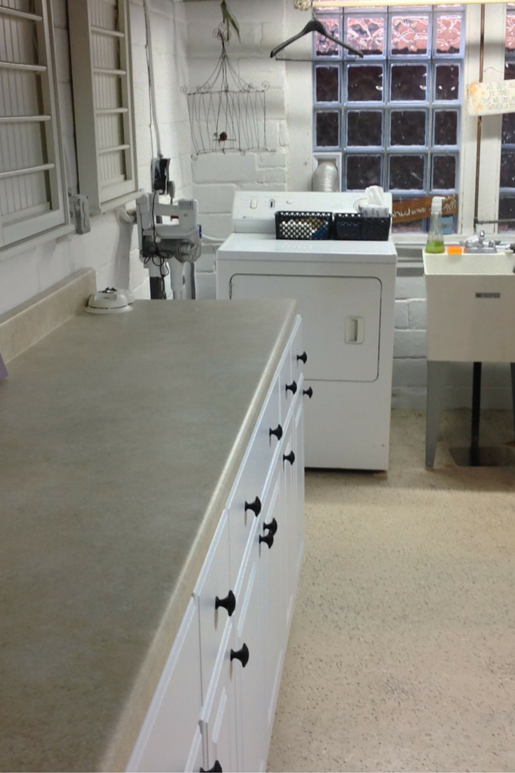 Finished laundry room with a long white counter and a large glass block window in university heights ohio