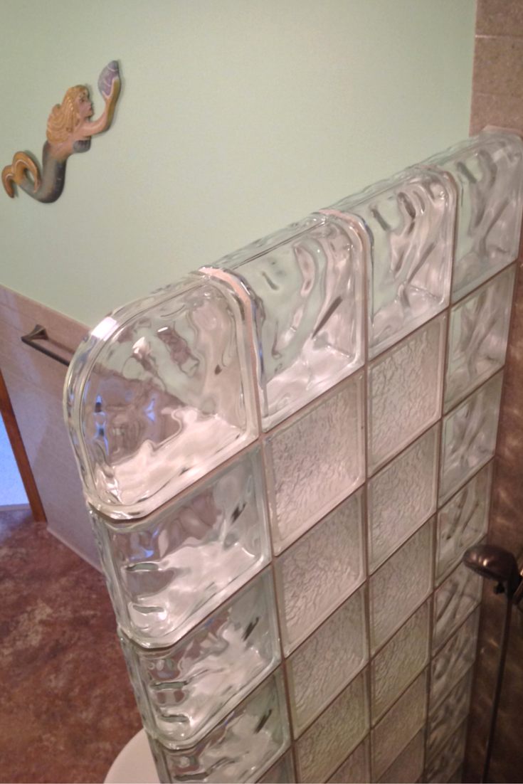 glass block shower wall with a finished end blocks and finished top with decora and icesapces pattern