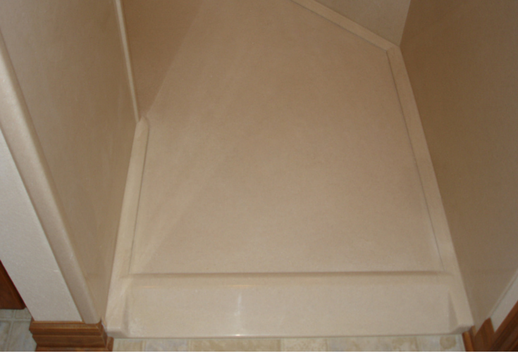 Solid surface shower pan with a ramped entry