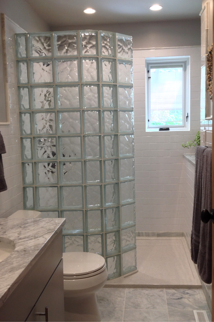 A curved glass block wall on a low threshold solid surface shower pan   Innovate Building Solutions