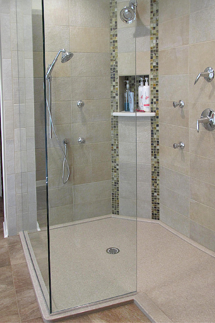 A frameless glass enclosure with a solid surface base