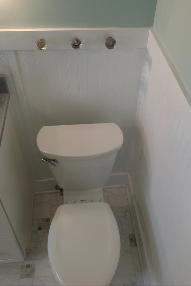 Repurposed door knobs which serve as towel holders behind a bathroom toilet