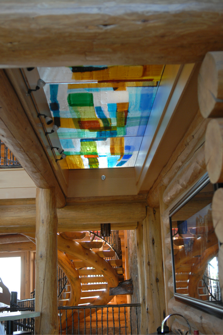Colored art glass bridge in a log home interior
