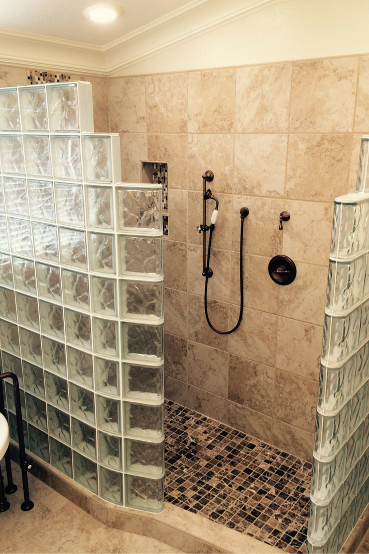 Walk in glass block shower with a curved and straight step down wall