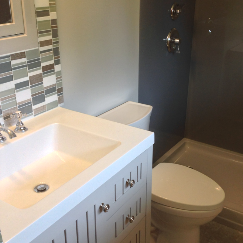 country vanity with modern high gloss acrylic shower walls in a columbus bathroom