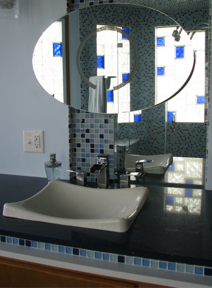 Mirrored reflection of a clear and colored glass block window in a contemporary bathroom | Innovate Building Solutions