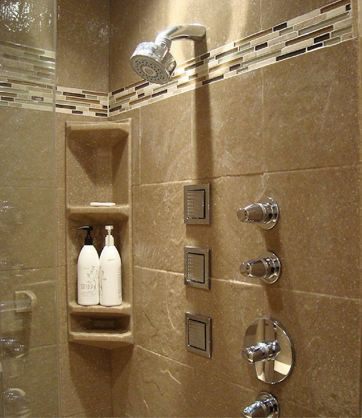This solid surface shower wall panel system has a tall corner caddy a glass tile border.