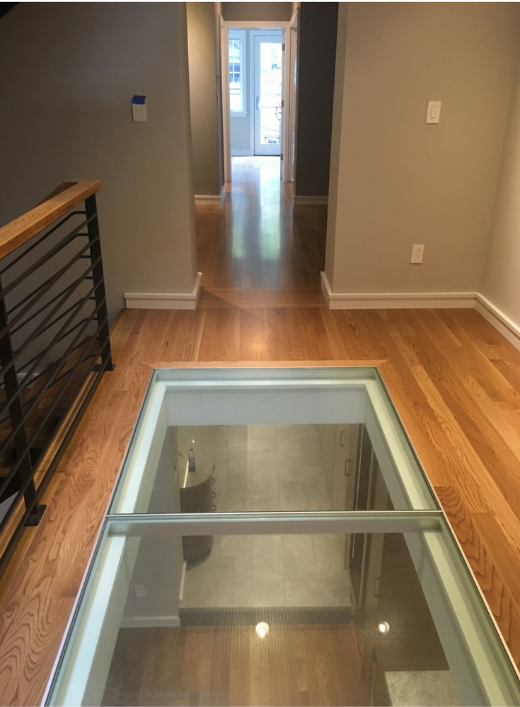 Pre-engineered glass flooring system with an aluminum grid around the perimeter of the glass